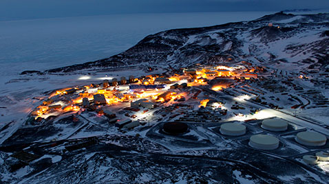 The skyline of McMurdo base at night, lit up it seems like a real town.